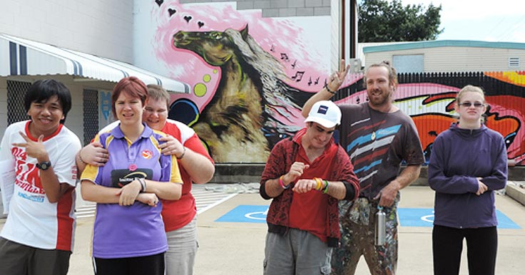 Aruma customers and a Disability Support Worker in front of their new mural