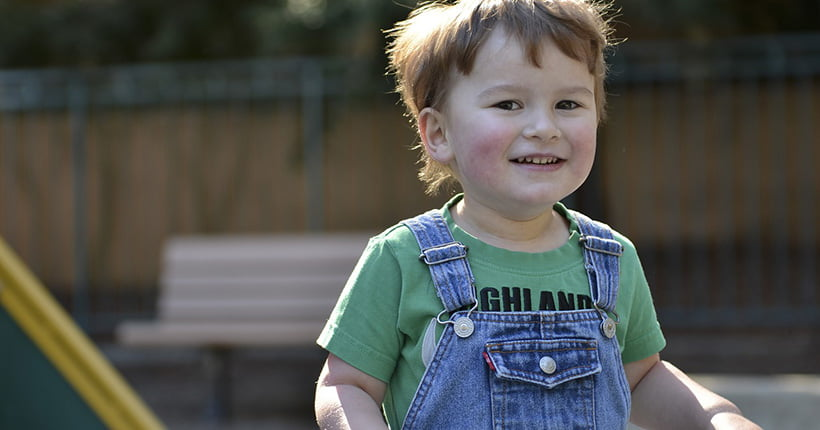 Young boy with autism smiling outside
