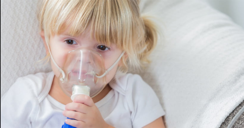 Girl with cystic fibrosis using a nebuliser