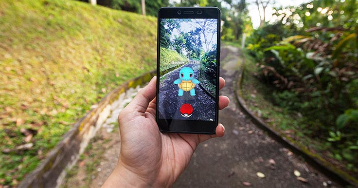 Person's hand holding a smartphone with Pokemon Go on the screen