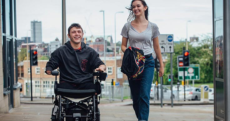 Woman and man in wheelchair chatting on the street