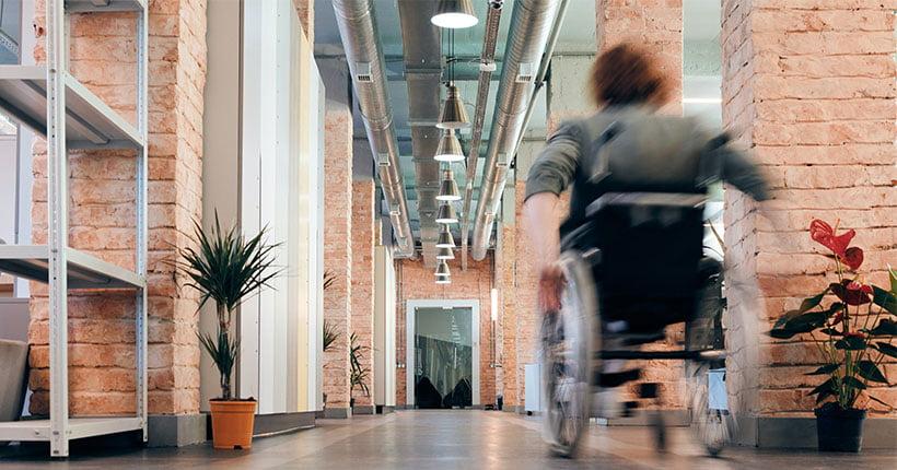 Woman in a wheelchair in a open plan office