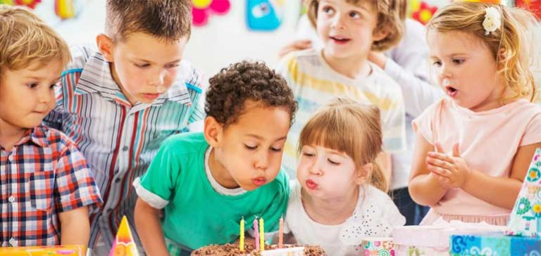 Group of kids at a birthday party blowing out candles