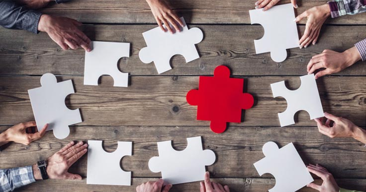 White puzzle pieces on a table with one red one in the middle