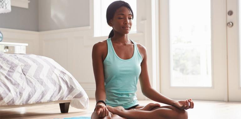 Lady sitting cross-legged on the floor meditating