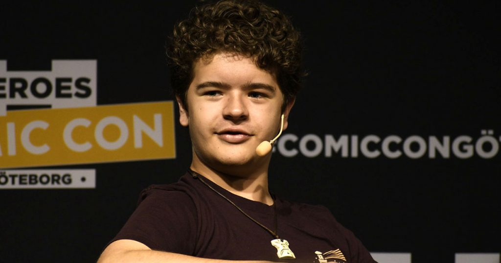 Gaten on a black background with a microphone on his head