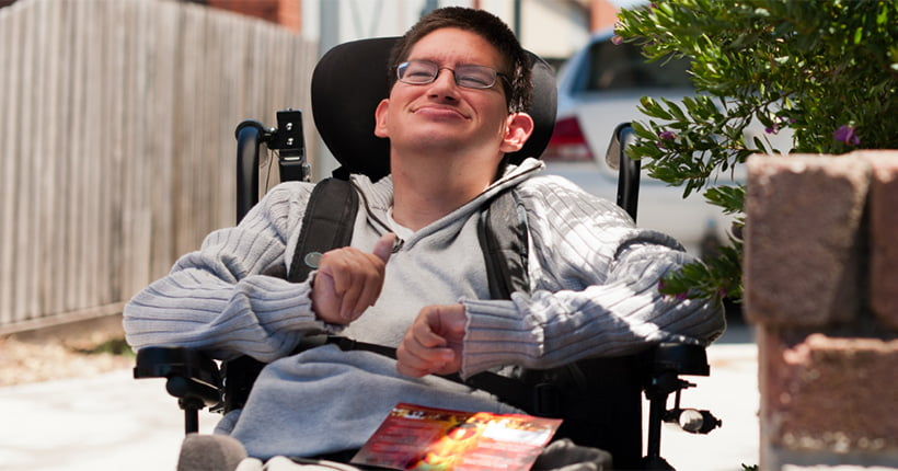 Young man who uses a wheelchair outside his house