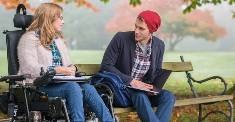 Young man and lady in wheelchair hanging out in the park