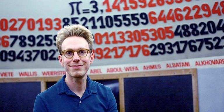 Daniel Tammet standing in front of the number pi
