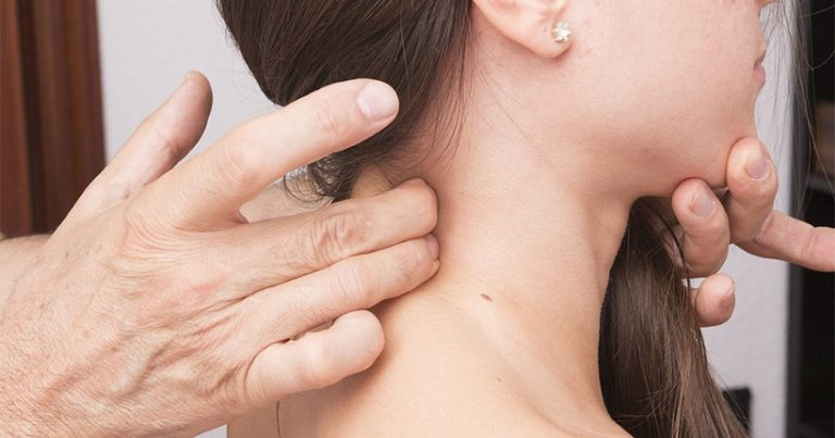 Woman in pain having someone press her neck with their fingers