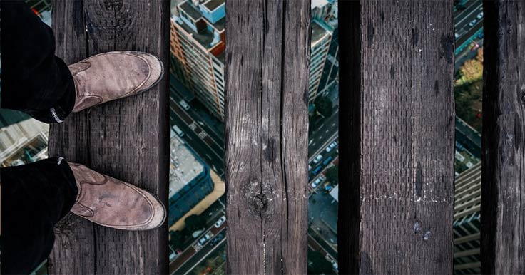 Photo looking at a person's feet standing on a high ledge