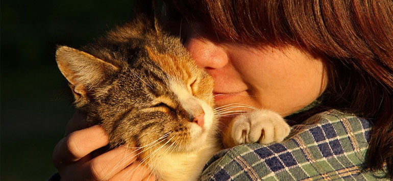 A woman hugging a cat closely