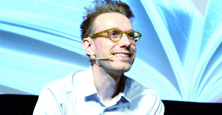 Daniel Tammet wearing a microphone and giving a speech