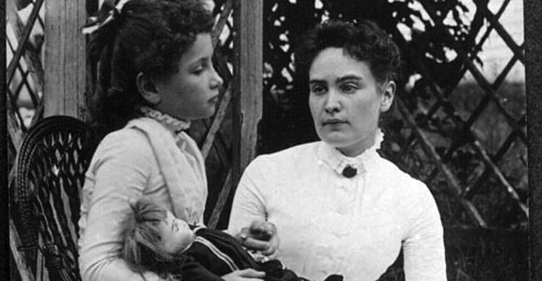 Helen Keller holding a doll while sitting with her Teacher, Anne Sullivan