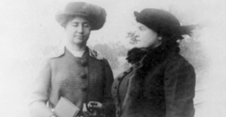 Helen Keller and Anne Sullivan standing outside in warm coats