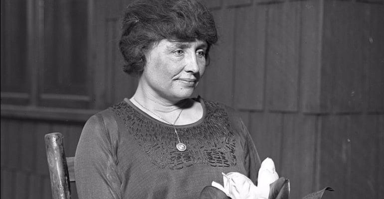Helen Keller holding a flower