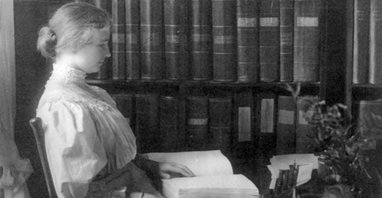 Helen Keller sitting reading a book in braille