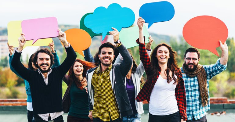 Group of people all holding colourful speech bubbles