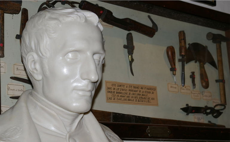 Bust of Louis Braille beside leathering equipment