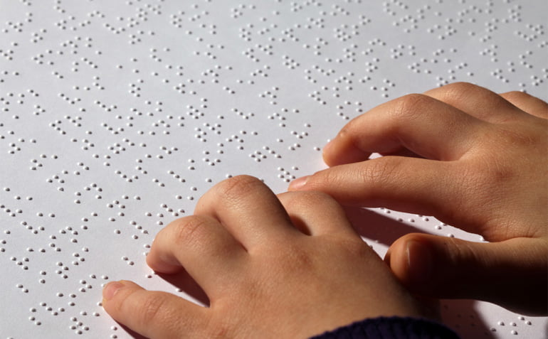 Close up of a child's hands while they read Braille