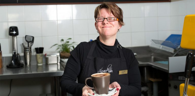Woman with a disability working in a cafe and holding a coffee