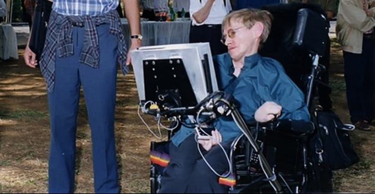 Stephen Hawking outside with his wheelchair and assistive device