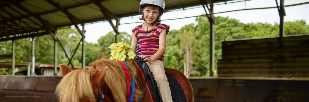 Young girl in a Children's disability Service, riding a horse