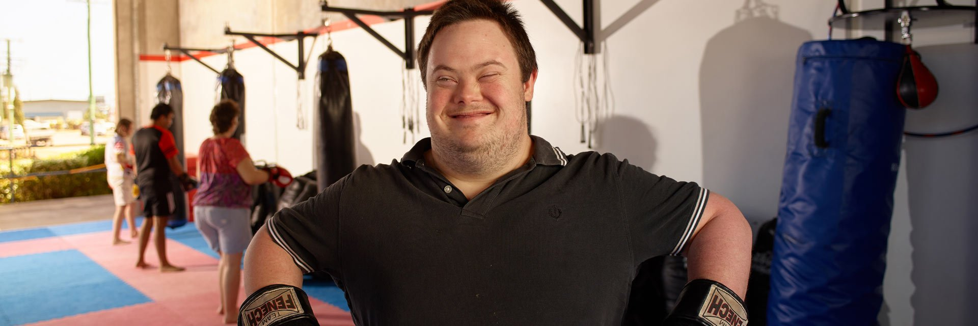 An Aruma customer with Down syndrome at the gym wearing boxing gloves