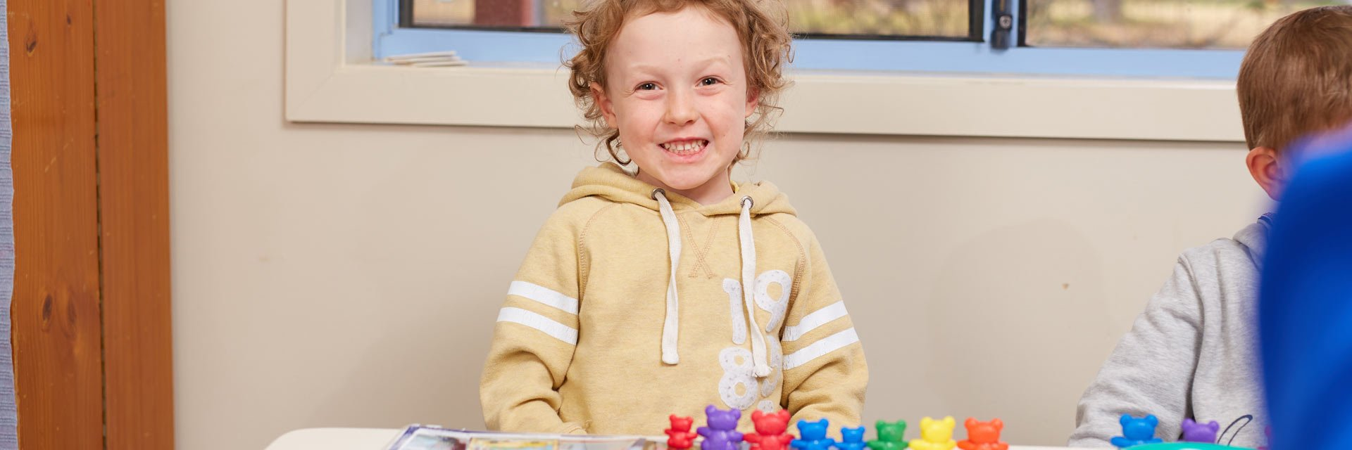 Young boy with a disability playing with toys in an Aruma Early Childhood Intervention service