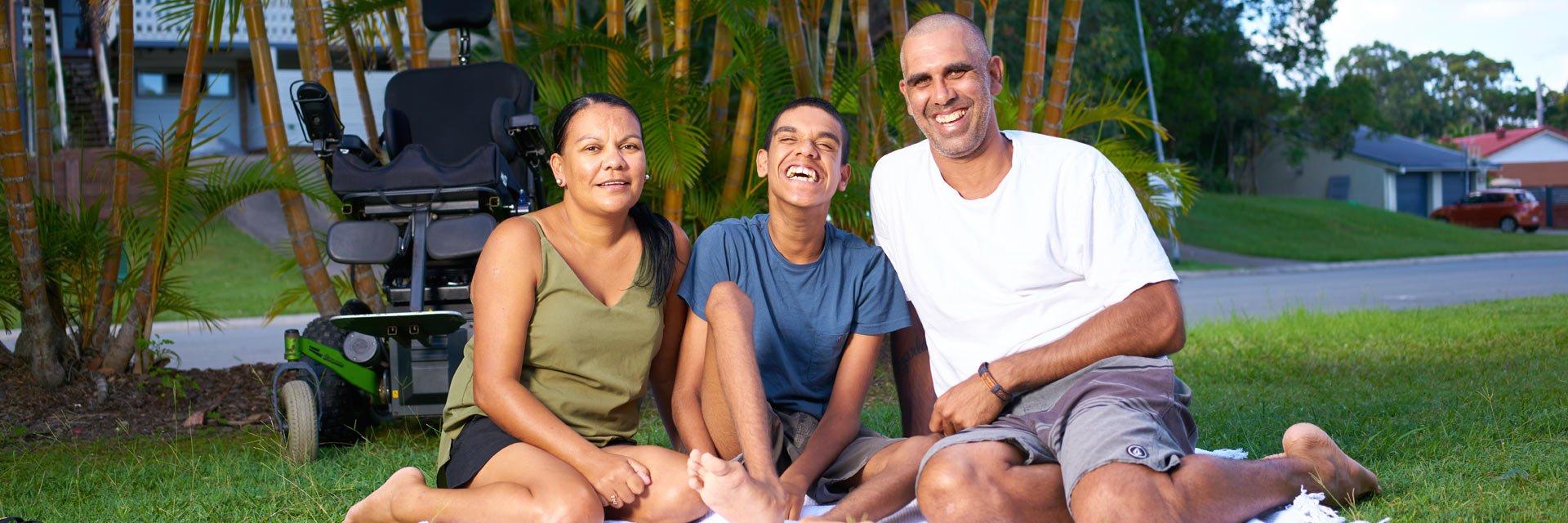 Aruma customer, Kobi and his family sitting outside on a picnic rug