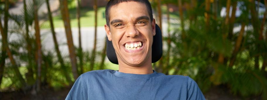 Kobi in his wheelchair smiling