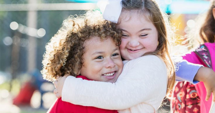 Girl hugging her sister with Down syndrome