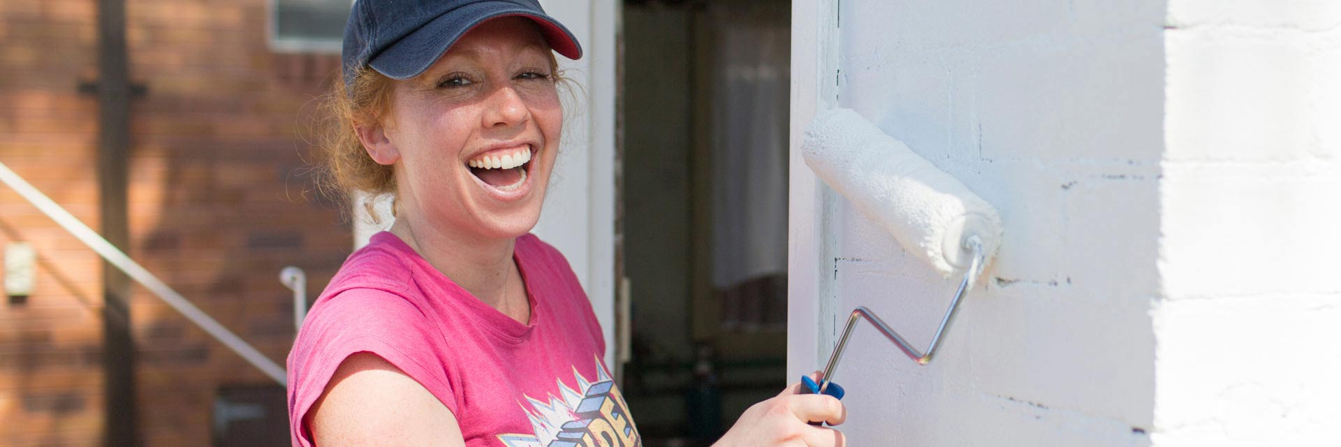 A corporate volunteer painting a wall with a roller