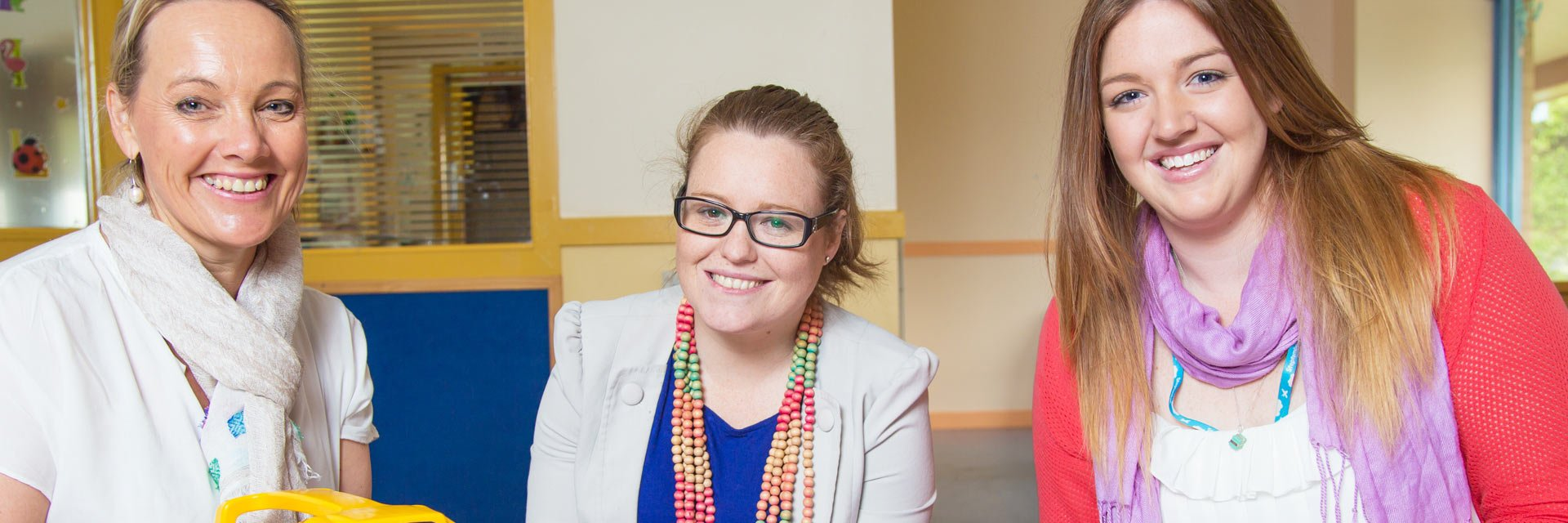 Three Disability Support Workers sitting at a table in a disability service