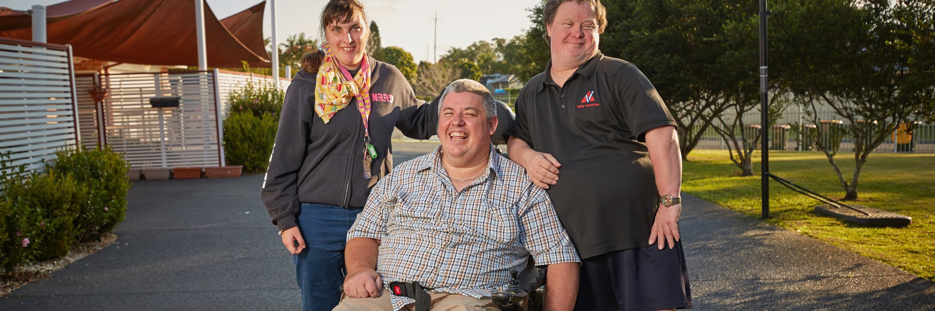Three people with a disability standing outside their Aruma disability service