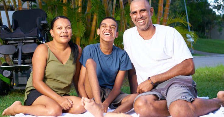 Man with a disability sitting outside on a picnic rug with his family
