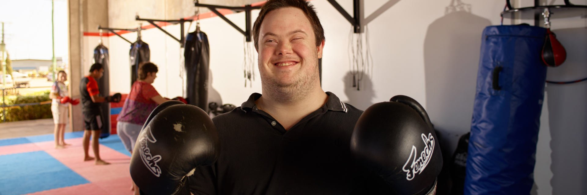 A man with down syndrome wearing boxing gloves