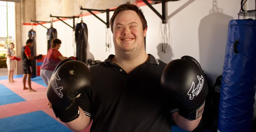 Man with Down syndrome wearing boxing gloves and smiling in a disability service