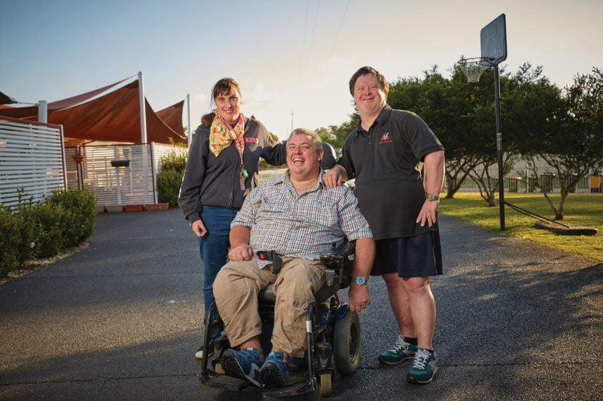 Three people with a disability outside a disability service smiling