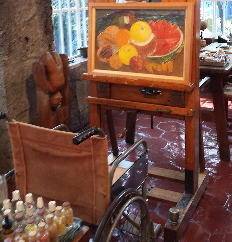 Kahlo's wheelchair and adjustable easel in La Casa Azul, with one of her still lifes from her final years