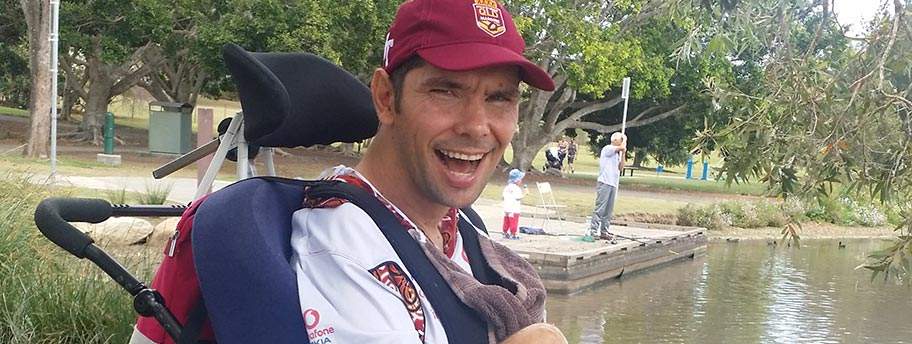 Clay smiling in a park, in front of a duck pond