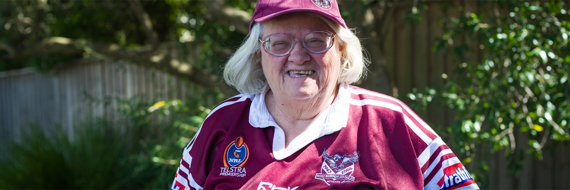 Woman with a disability wearinga Manly Sea Eagles jersey and standing outside