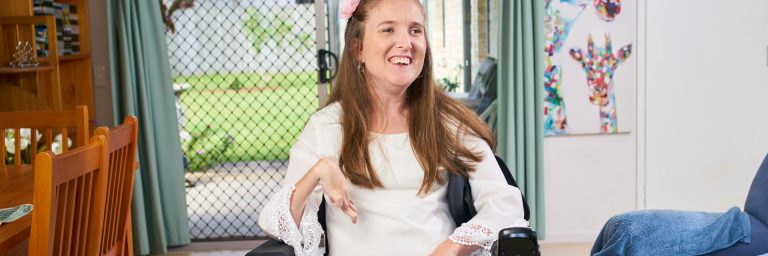 Woman who uses a wheelchair in a house which includes home modifications