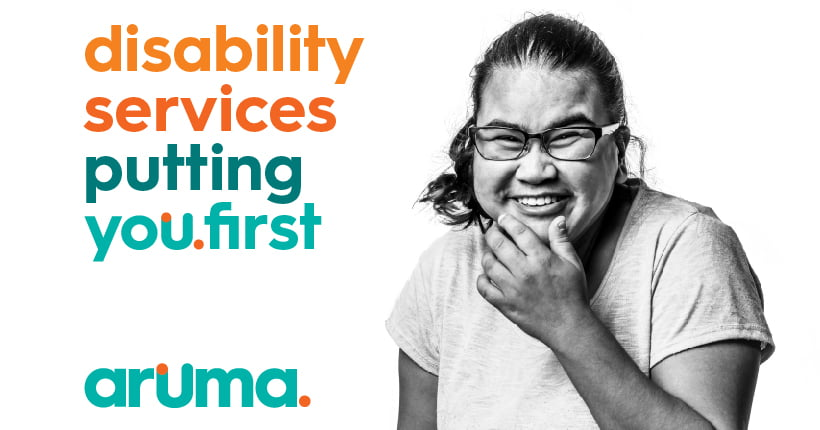 An Aruma customer with a disability with the words 'disability services putting you first'
