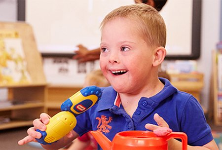 Child with Down syndrome playing with toys