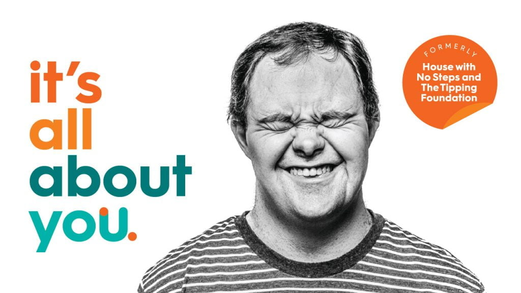 Man with down syndrome smiling and the text written in rainbow colours saying 'it's all about you'