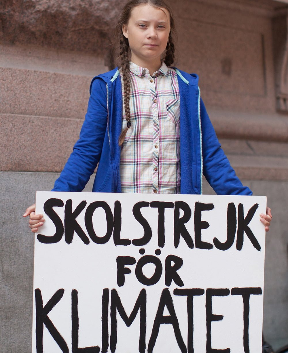 Greta Thunberg protesting and holding a sign reading 'School Strike for Climate' in English