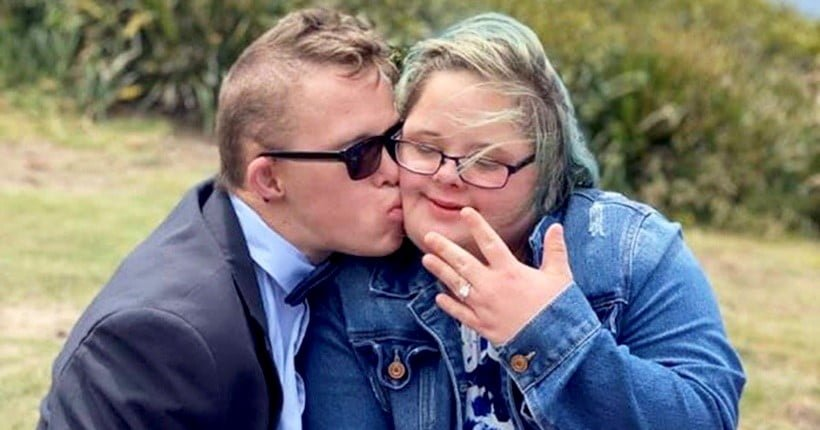 Mitch and Jacqui, a couple with Down syndrome, together after they became engaged. Mitch is kissing Jacqui on her cheek and Jacqui is holding up her hand showing off her ring.