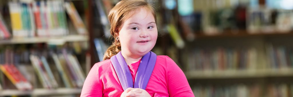 Girl with Down syndrome standing in a library with a backpack