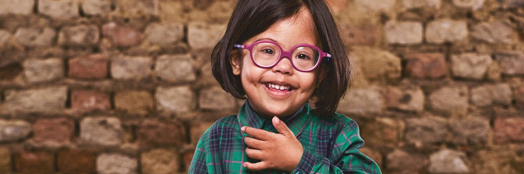 Girl with Down syndrome wearing glasses and standing in front of a brick wall
